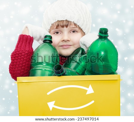 cute young girl with plastic bottles in recycle bin on winter background - waste sorting theme - stock photo