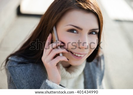 Cute young girl with pug nose talking on the phone at bright spring day outdoors. The model is beautiful and the smart phone is modern - stock photo