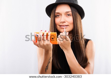 Cute young girl, with straight dark hair, wearing on hat and black blouse, holding smart phone and making make-up, against white background, waist up