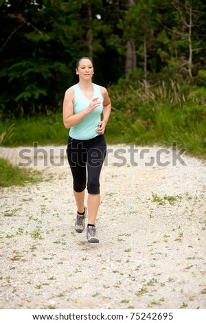 Cute young girl works out in nature and runs through forest
