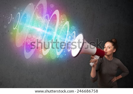 Cute young girl yells into a loudspeaker and colorful energy beam comes out - stock photo