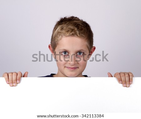 Cute young happy boy holding a blank board against white background - stock photo