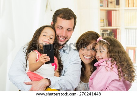 Cute young happy family with two little girls taking a selfie photo - stock photo