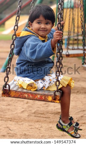 Cute young happy indian girl ( kid ) playing on a swing in a park. The photo shows summer time playground with a female child smiling and sitting on a swing - stock photo