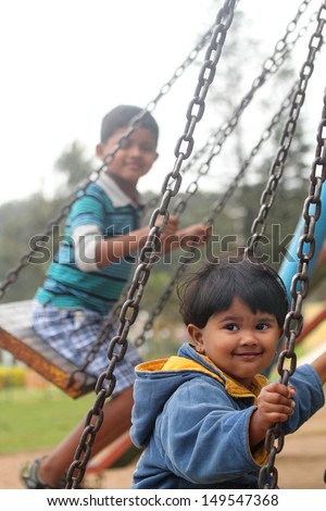 Cute young happy kids playing on swing sets in a park. The photo shows summer time playground with a boy and a girl swinging and enjoying their leisure time - stock photo