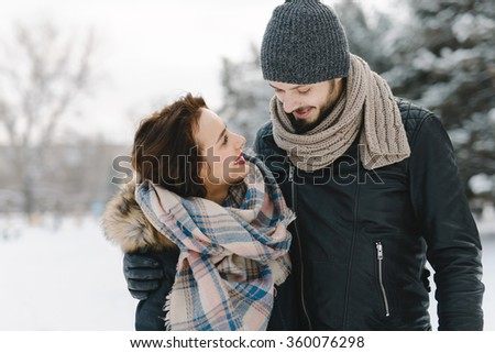 Cute young hipster couple having fun in winter park on a bright day hugging each other and smiling