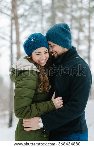 Cute young hipster couple having fun in winter park warming each other on a bright day hugging each other and smiling