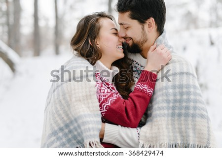 Cute young hipster couple having fun in winter park warming eachother on a bright day hugging each other and smiling   - stock photo