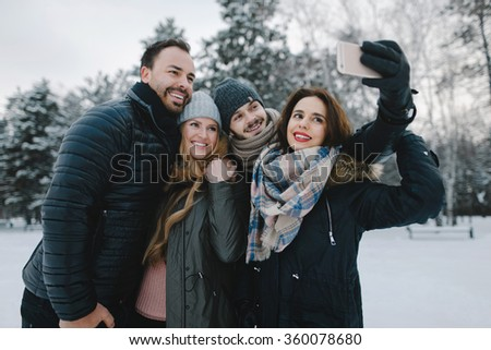 Cute young hipster couples posing in winter park on a bright day hugging each other and smiling  - stock photo