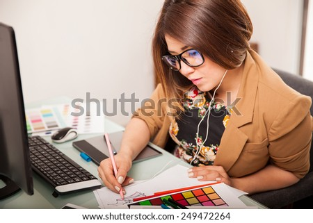 Cute young Hispanic designer working on some sketches while listening to music - stock photo