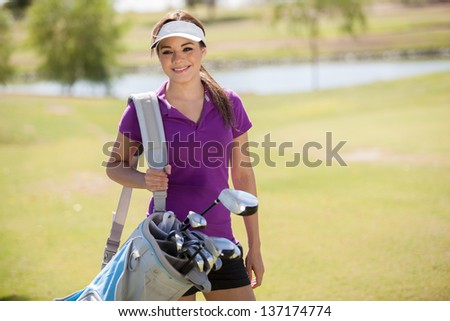 Cute young Hispanic woman carrying a golf bag and smiling - stock photo