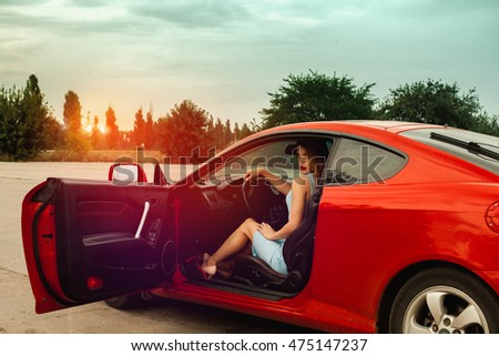 cute young lady with red lips sits in red sport car and looking at the camera at sunset