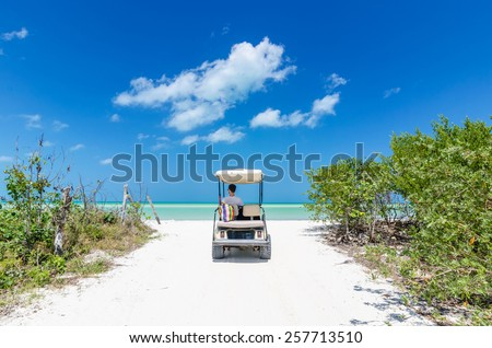 Cute young man driving on a golf cart back view at tropical white sandy beach during Caribbean vacation on Holbox island, Mexico - stock photo