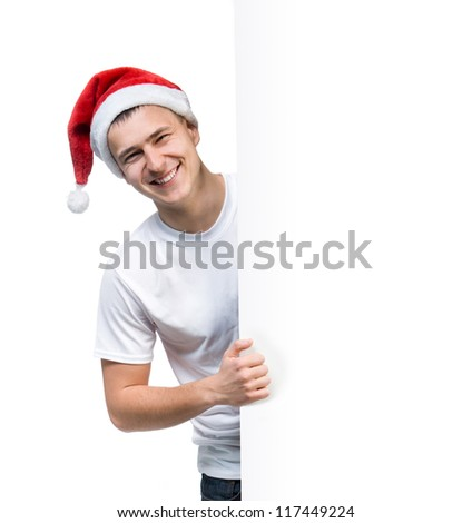 cute young man in a Santa Claus hat behind the white board with space for text - stock photo
