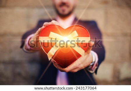 Cute young man with smile holding a heart shape Valentines gift out to you - stock photo
