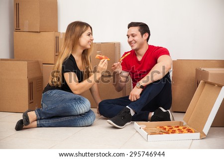 Cute young married couple eating pizza while moving and unpacking in their new home - stock photo