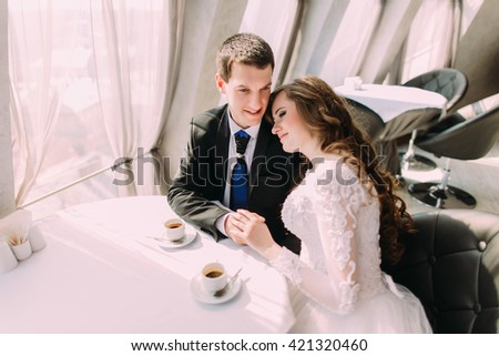 Cute young married couple hugging sitting in coffee shop - stock photo