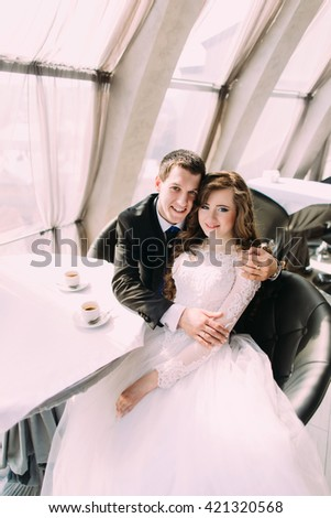 Cute young married couple hugging sitting in coffee shop and looking at the camera - stock photo