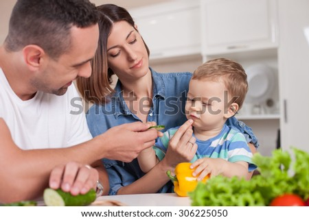 Cute young married couple is feeding their little son with vegetables. They are sitting at the table and smiling. The woman is holding a kin on her knees. The boy tastes healthy food with interest - stock photo