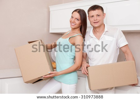 Cute young married couple is standing in kitchen and holding boxes in their hands. They are moving in a new building. They are smiling happily and looking at the camera with joy