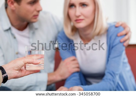 Cute young married couple is visiting female psychologist. The woman is crying with frustration. The man is trying to calm her down and embracing. Lady is giving her glass of water - stock photo