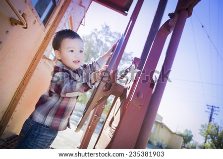 Cute Young Mixed Race Boy Having Fun Outside on Railroad Car.
