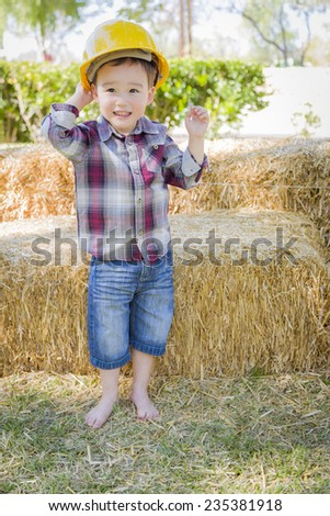 Cute Young Mixed Race Boy Laughing with Hard Hat Outside Near Hay Bale. - stock photo