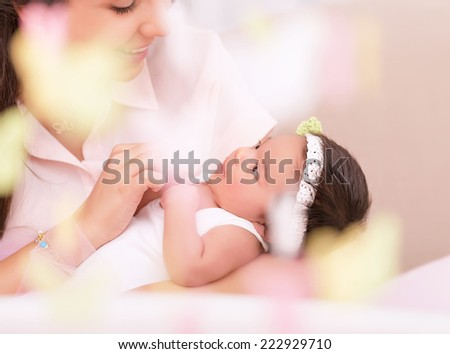 Cute young mother looking on sweet newborn daughter, take care about her, photo with soft focus, happy motherhood concept  - stock photo