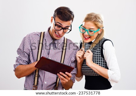 Cute young nerds using digital tablet,Nerds using digital tablet - stock photo