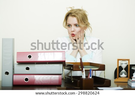Cute young overworked secretary girl with blond curly hair has stress sitting at table with many folders documents and office appliances on white background copyspace, horizontal picture