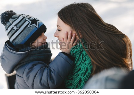 Cute young pregnant mother and her child having fun in winter park on a bright day hugging each other and smiling  - stock photo
