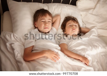 Cute young preschool brother and sister sleeping together in bed. - stock photo