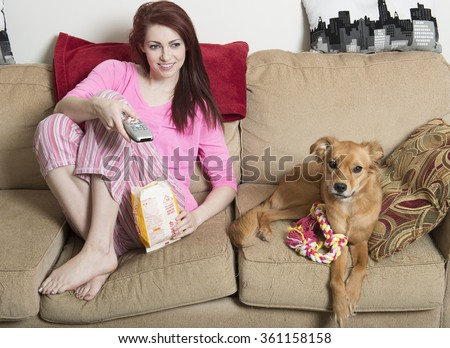 Cute young red-haired woman in pink pajamas sitting in living room eating popcorn with her adorable dog next to her on couch - watching tv - stock photo