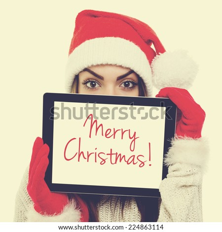 Cute young Santa Claus woman with digital tablet. Beautiful teenage girl with hat and gloves showing tablet with Merry Christmas text. Square format image with instant filter look. - stock photo