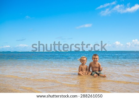 Cute young siblings sitting in ocean together