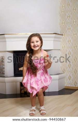 cute young smiling girl in pink dress standing near fireplace at home with sweet