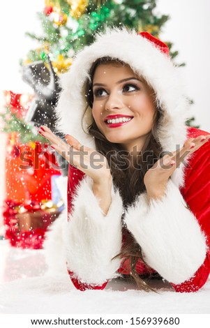 Cute young smiling woman wearing a Christmas costume enjoying the falling snow while lying on the ground. - stock photo
