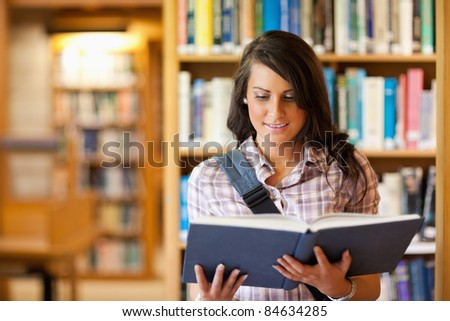 Cute young student reading a book in the library - stock photo