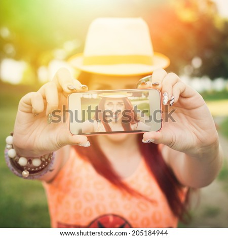 Cute young teenage woman taking a selfie with smart phone. Beautiful redhead ginger teenage girl taking a picture of herself outdoors in park on sunny summer day. Square format image. - stock photo