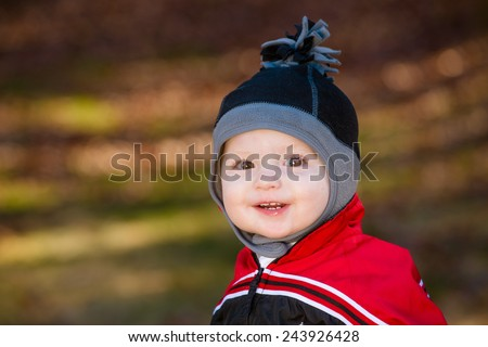 Cute young toddler dressed for cold weather with winter hat - stock photo