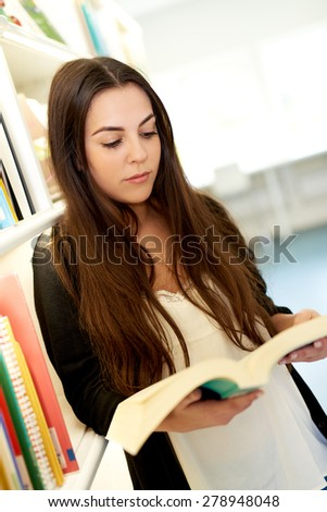 Cute young university student looking up information leaning against a bookshelf full of books reading from a thick soft cover text book - stock photo