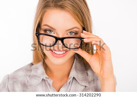 cute young woman adjusting her glasses and smiling