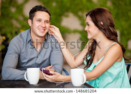 Cute young woman and her date listening to some music together at a terrace