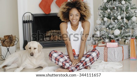 Cute young woman and her dog at Christmas sitting together on the floor in front of the decorated tree with gifts smiling happily at the camera.
