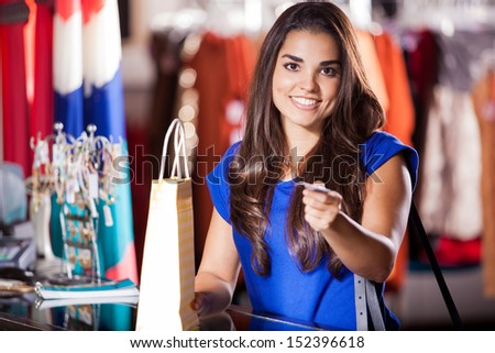 Cute young woman doing some shopping with a credit card and smiling - stock photo