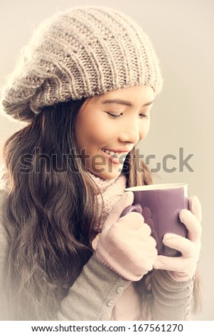 Cute young woman drinking tea on a cold winter day. - stock photo