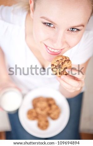 Cute young woman eating cookies and drinking milk, vertical picture from above, model is smiling into the camera - stock photo
