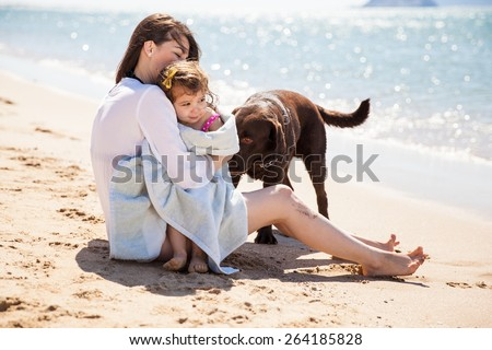 Cute young woman enjoying the sun at the beach with her daughter and dog after a swim - stock photo