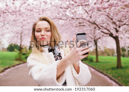 Cute young woman gesturing peace sign while taking her picture with mobile phone. Caucasian female model at spring blossom park taking self portrait with smart phone. - stock photo