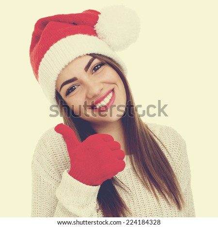 Cute young woman gesturing thumbs up. Beautiful Christmas woman smiling wearing Santa Claus hat and gloves. Square format image with instagram filter. - stock photo
